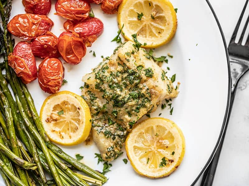 Overhead view of Garlic Butter Baked Cod on a plate with tomatoes and asparagus, a black fork on the side.