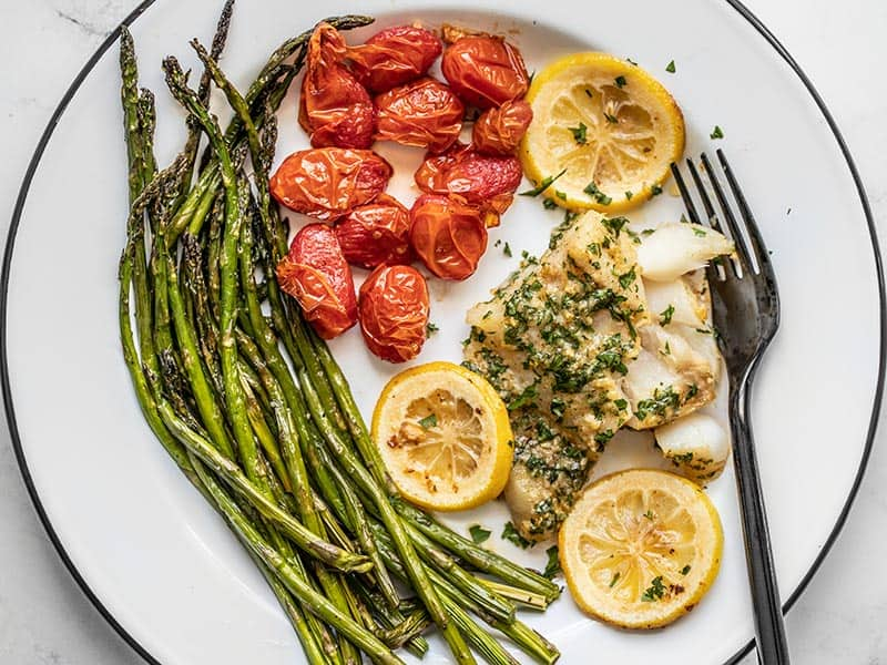 Overhead view of the plate full of tomatoes, asparagus, and Garlic Butter Baked Cod.