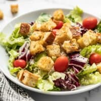 Front view of a large salad in a bowl topped with homemade croutons