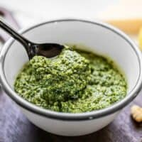 Side view of a spoonful of kale pesto being lifted from the bowl.