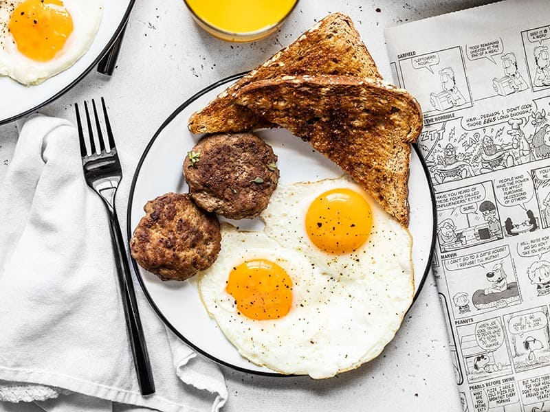 A breakfast plate with eggs, toast, and maple sage breakfast sausage, next to a newspaper and glass of orange juice.
