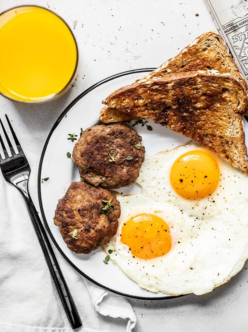Two maple sage breakfast sausage patties on a plate with eggs and toast, and a glass of orange juice on the side.