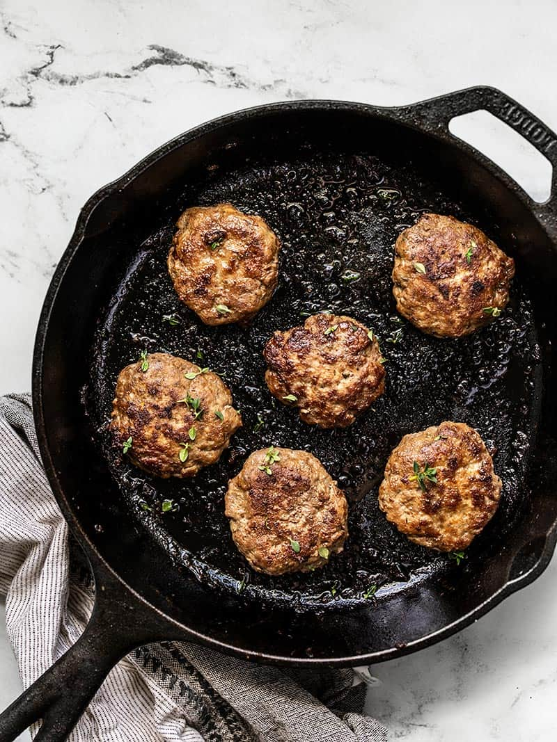 Overhead of a cast iron skillet with five cooked Maple Sage Breakfast Sausage patties