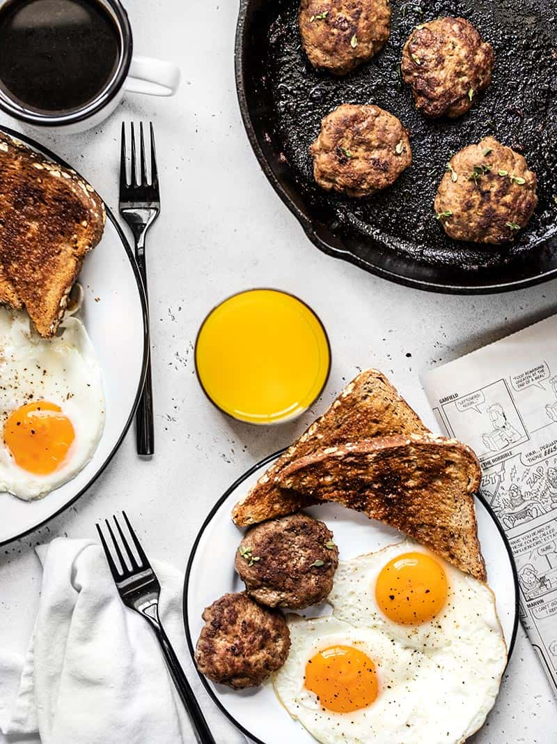 Tablescape with two plates full of eggs, toast, and maple sage breakfast sausage, a cast iron skillet with sausage, and drinks