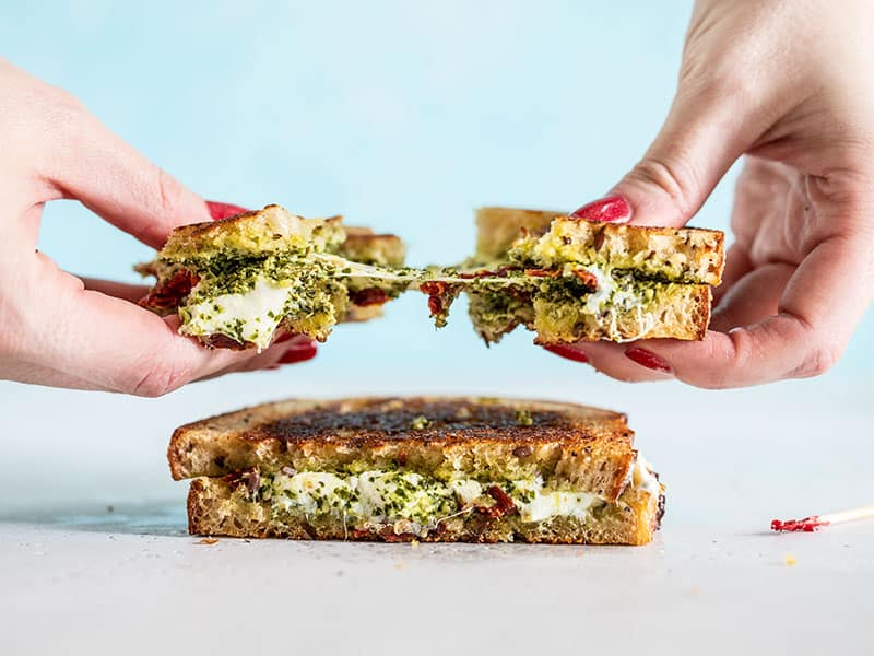 Two hands pulling the pesto grilled cheese sandwich in half, with the cheese pulling between and sun dried tomato pieces exposed.