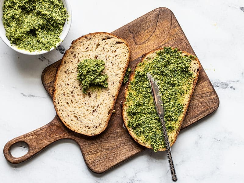 Pesto being spread onto two slices of bread, a bowl of pesto on the side.