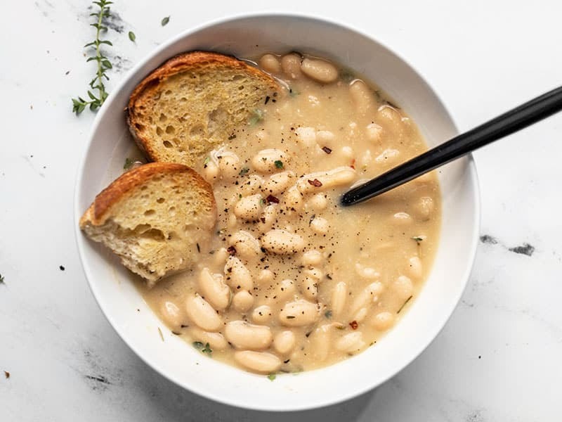 A bowl of Rosemary Garlic White Bean Soup with two pieces of toasted bread and a black spoon in the middle.