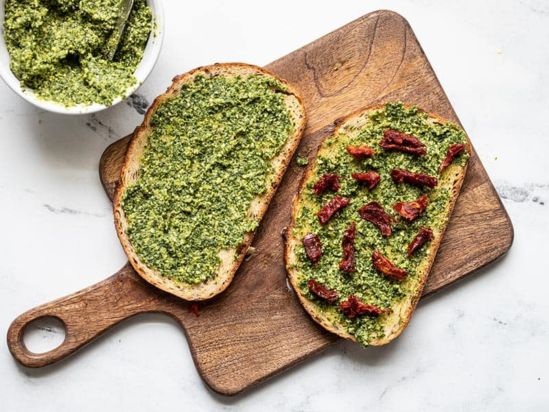 Sun dried tomato pieces added to pesto on bread.