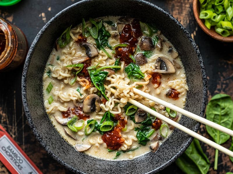 Close up overhead view of a bowl full of vegan creamy mushroom ramen with chopsticks lifting some noodles