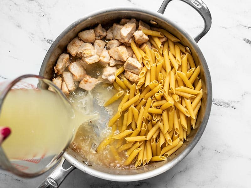 Uncooked pasta and chicken broth added to the skillet