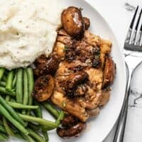 Close overhead view of Balsamic Chicken and Vegetables on a plate with mashed potatoes and green beans