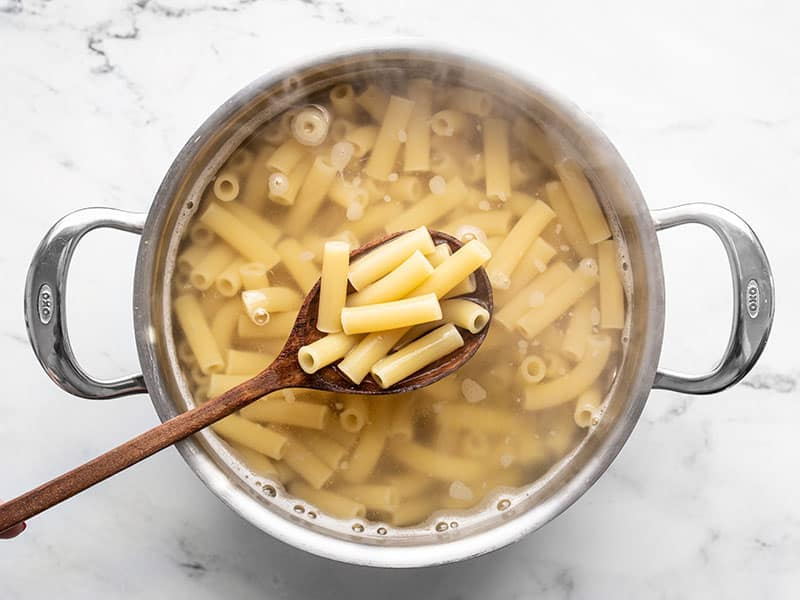 Boiled ziti in a pot of water with a wooden spoon