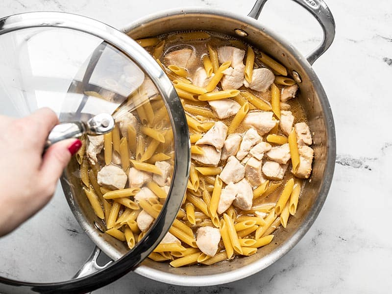 Lid being placed on the skillet with uncooked pasta and chicken