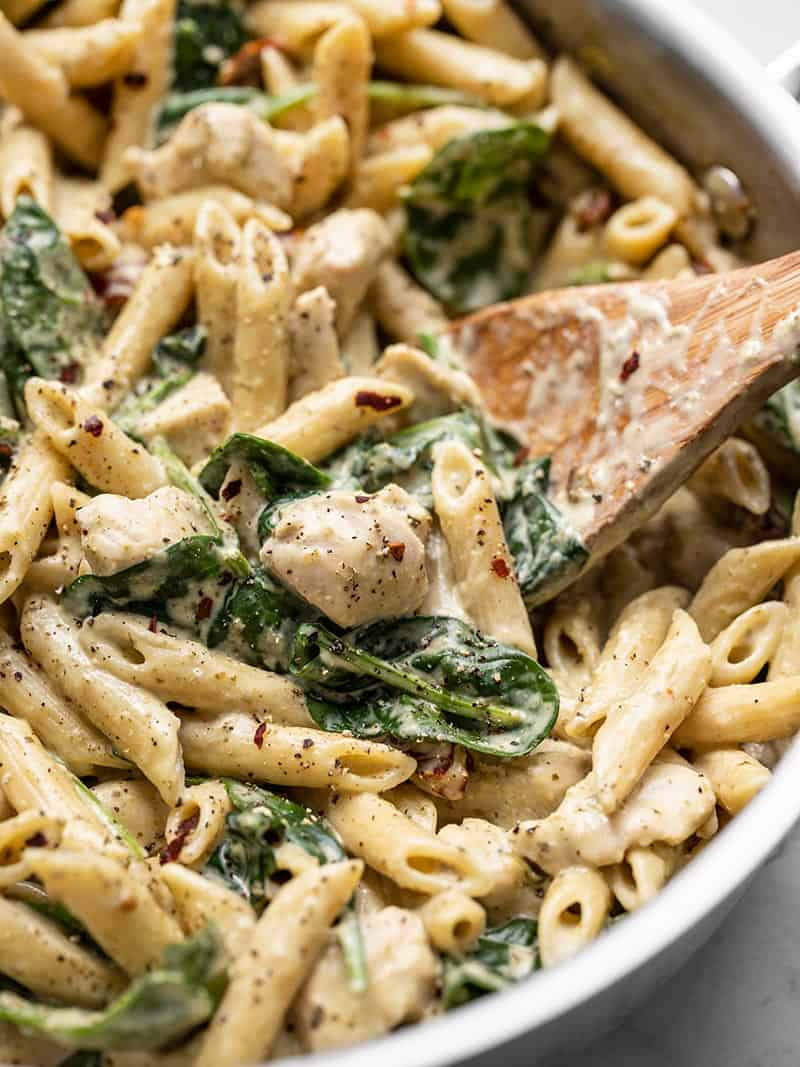 Close up of One Pot Creamy Pesto Chicken Pasta in the skillet with a wooden spoon