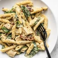 Close up of one pot creamy pesto chicken pasta in a shallow bowl with a black fork.