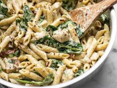 Close up of One Pot Creamy Pesto Chicken Pasta in the skillet with a wooden spoon.