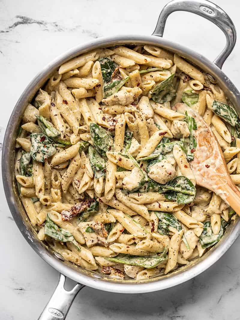 Overhead view of a skillet full of one pot creamy pesto chicken pasta with a wooden spoon in the side.