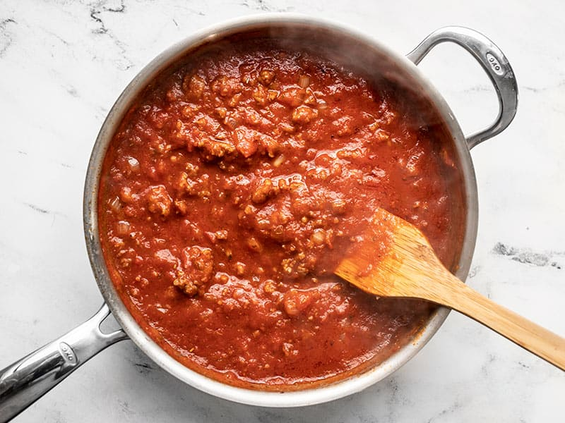 Red meat sauce in a skillet with a wooden spatula