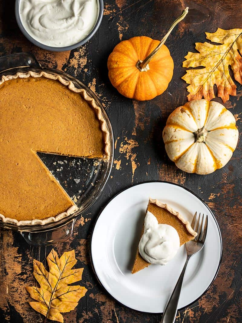 Overhead view of a Maple Brown Butter Pumpkin Pie with a slice cut out, on a plate, with whipped cream on top.