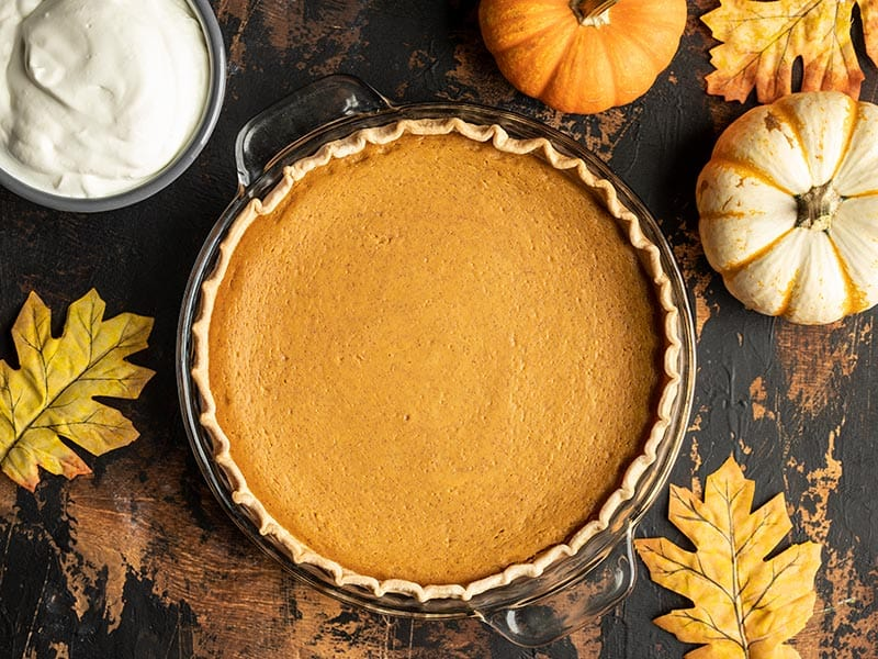 Overhead view of a baked Maple Brown Butter Pumpkin Pie, uncut with whipped cream, mini pumpkins, and leaves on the side.