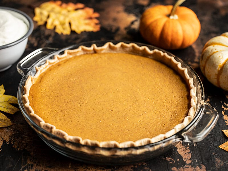 Baked Maple Brown Butter Pumpkin Pie with mini pumpkins in the background