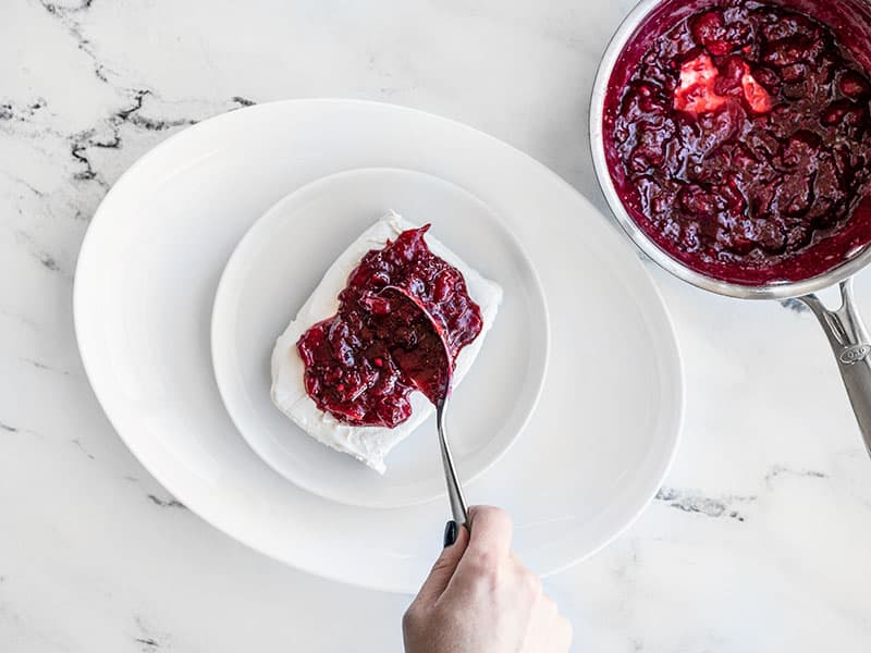 Cranberry Sauce being spooned onto cream cheese