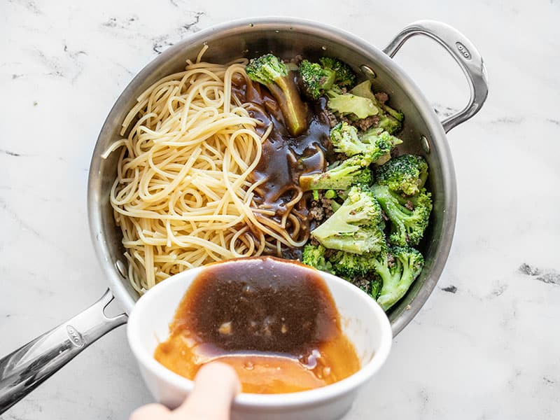 Spaghetti and sauce added to the skillet with beef and broccoli