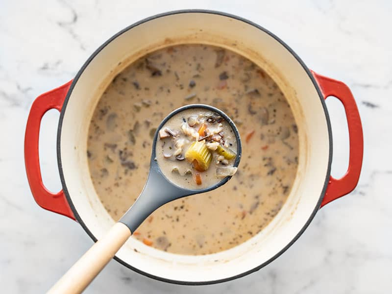 Finished Creamy Vegetable Wild Rice Soup in a ladle above the soup pot