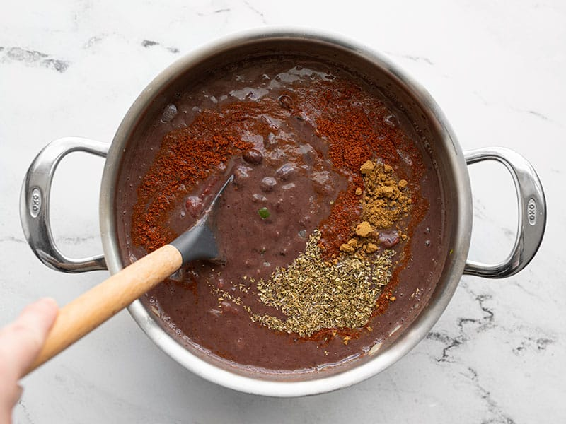 Spices being stirred into black bean soup