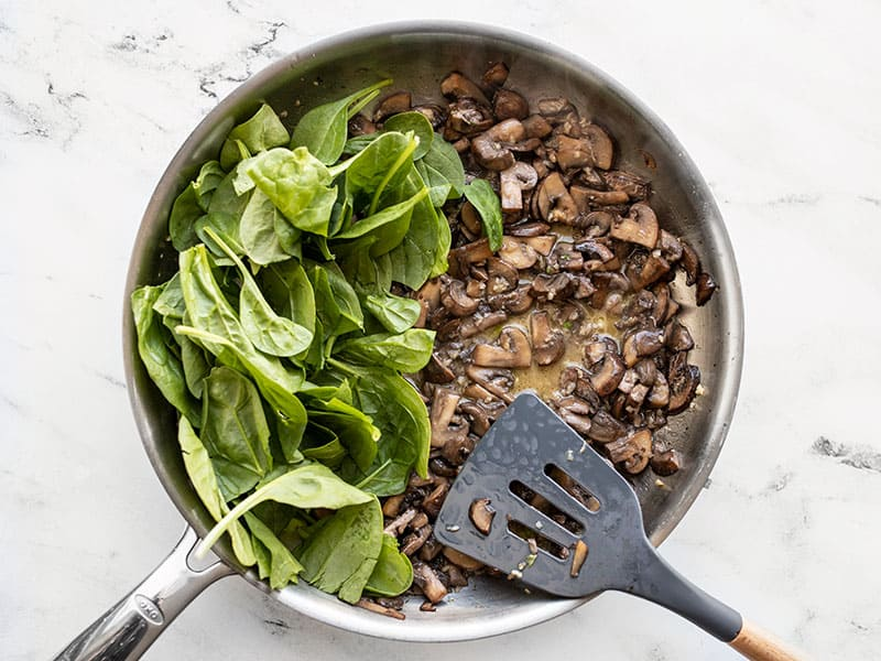 Add spinach and starchy water to skillet