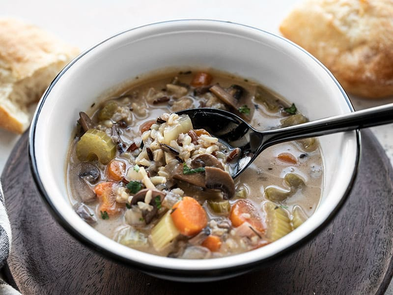 Front view of a bowl of creamy vegetable wild rice soup with a spoon lifting some out of the bowl