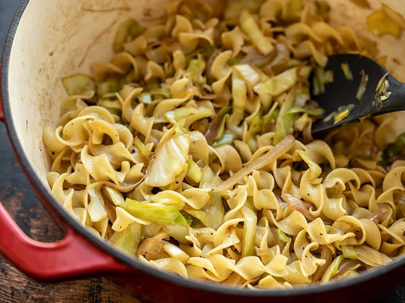 Close up of fried cabbage and noodles in a large pot, from the side