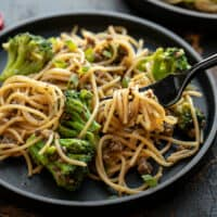 Close up of a fork twirling some Garlic Noodles with Beef and Broccoli on a black plate
