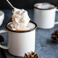 Homemade whipped cream being spooned onto a mug of hot cocoa, a second mug in the background