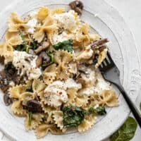 Close up of Mushroom and Spinach Pasta with Ricotta on a plate with a black fork.