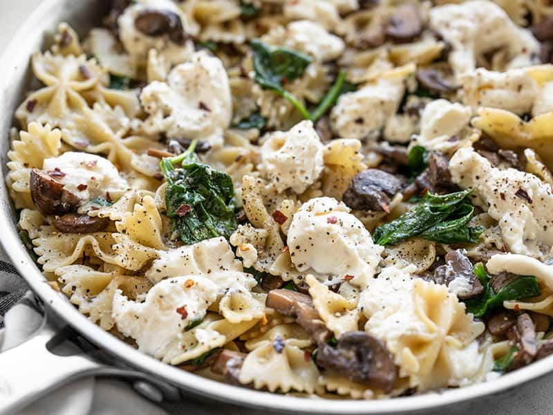 Close up of Mushroom and Spinach Pasta with Ricotta in the skillet, from the side.