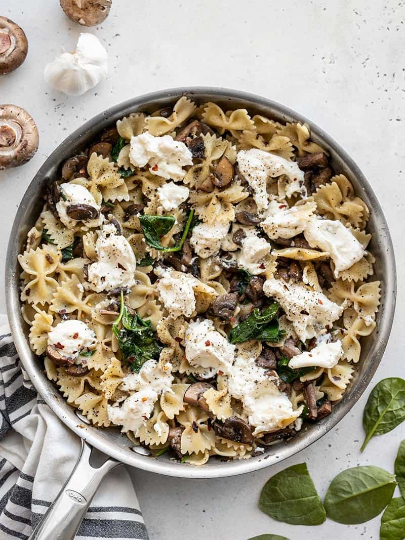 A skillet full of Mushroom and Spinach Pasta with Ricotta with spinach leaves and whole mushrooms on the sides