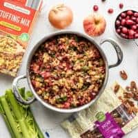 Overhead view of a pot full of Roasted Apple Cranberry Cornbread Stuffing with ingredients scattered all around