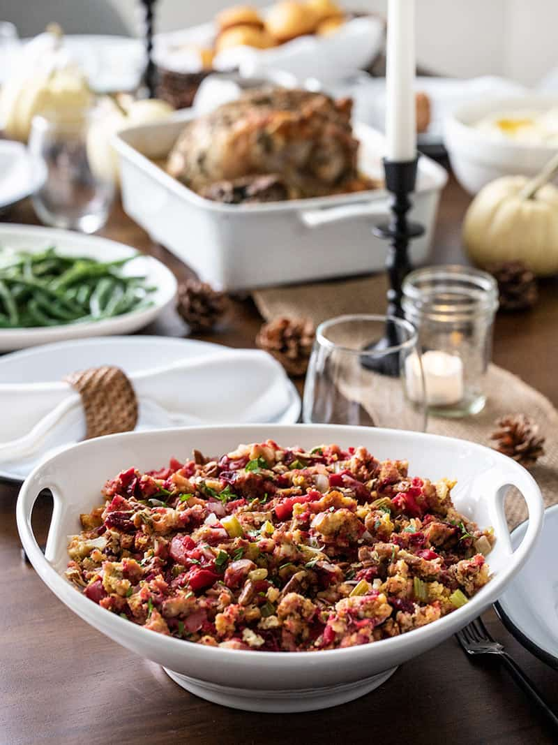 Roasted Apple Cranberry Cornbread Stuffing on a Thanksgiving table with other dishes in the background