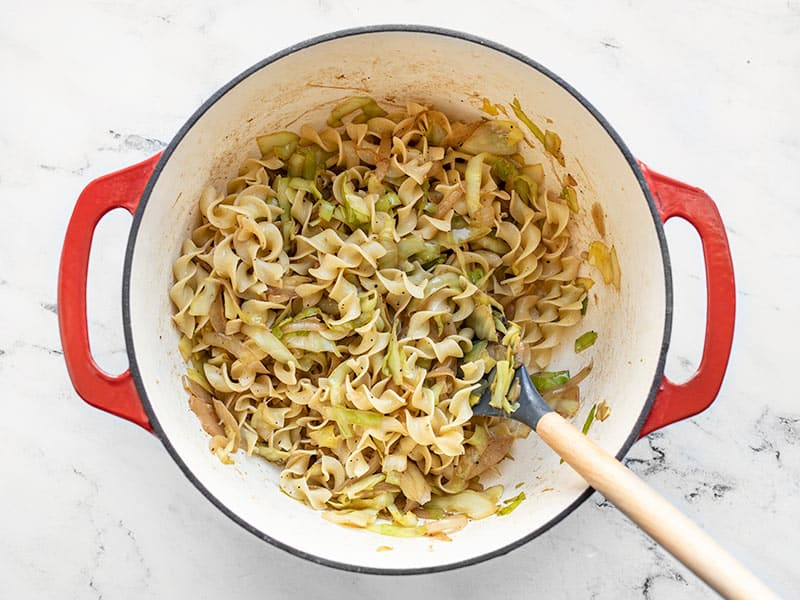 Finished fried cabbage and noodles in the pot with a spoon