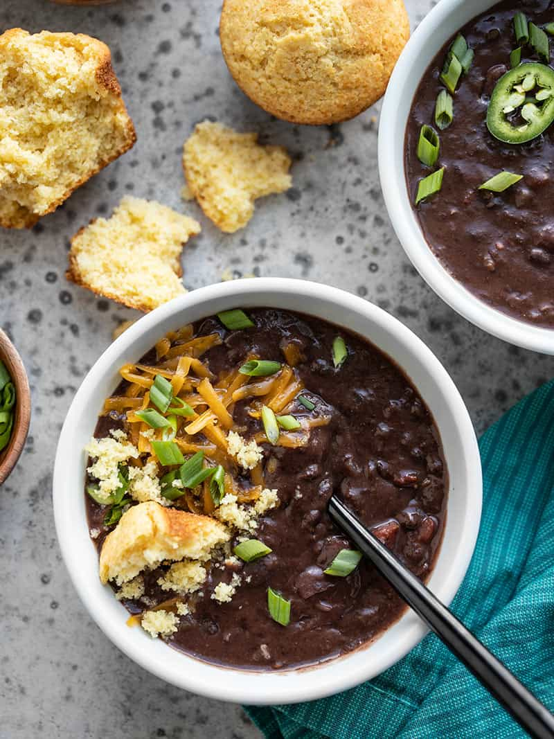 Two bowls of Smoky Black Bean Soup with different toppings, like cornbread, jalapeño, cheddar, and green onion