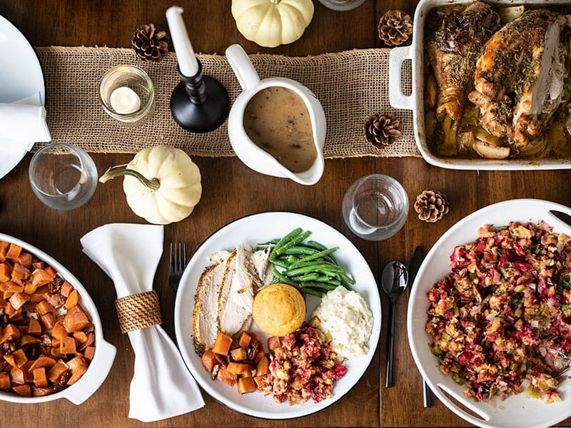 A full Thanksgiving dinner plate on a table with other Thanksgiving dishes