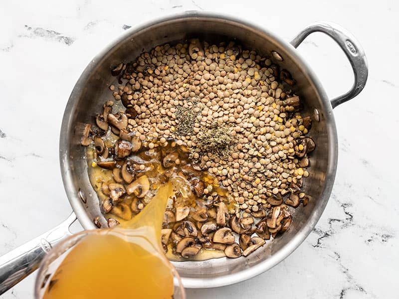 Lentils, herbs, and broth added to mushrooms in the skillet