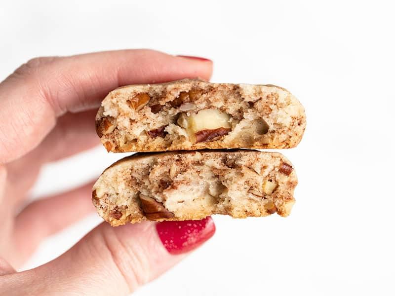 A cinnamon pecan sandie broken in half held close to the camera to show the inside texture.