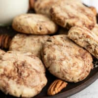 Close up of Cinnamon Pecan Sandies on a wooden plate with whole pecans
