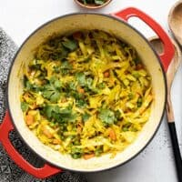 Curried Cabbage in a red pot with wooden utensils on the side.
