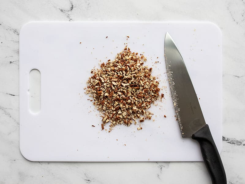 Finely chopped pecans on a cutting board with a knife.
