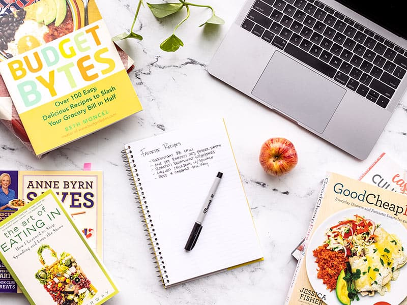 A notebook with a list of recipes surrounded by cookbooks and a laptop.