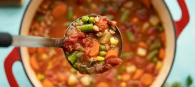 Close up of a ladle full of Vegetable Barley Soup being held over the soup pot.