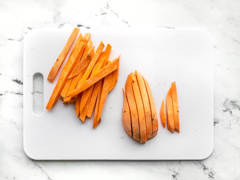 Sliced sweet potatoes into fries on cutting board